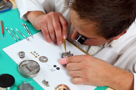 watchmaker: Watchmaker in his workshop repairing a wrist watch. Intentional shallow depth of field