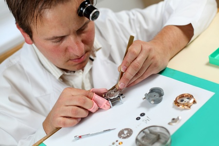Watchmaker in his workshop repairing a wrist watch. Intentional shallow depth of field