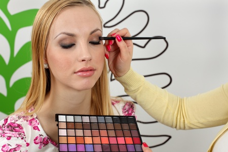 Professional makeup artist applying makeup to attractive young woman face photo