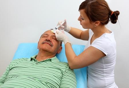 wrinkly: Older man receiving botox injection in his wrinkles
