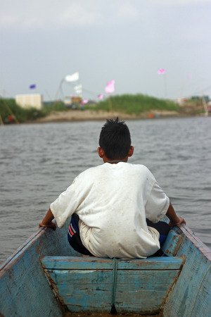 let go: asian young boy in rowboat Stock Photo