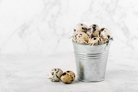 Bucket with  quail  eggs on a marble background.