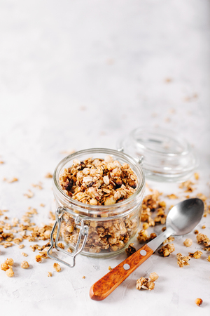 avena en hojuelas: Homemade granola with nuts and seeds in glass jar for healthy breakfast