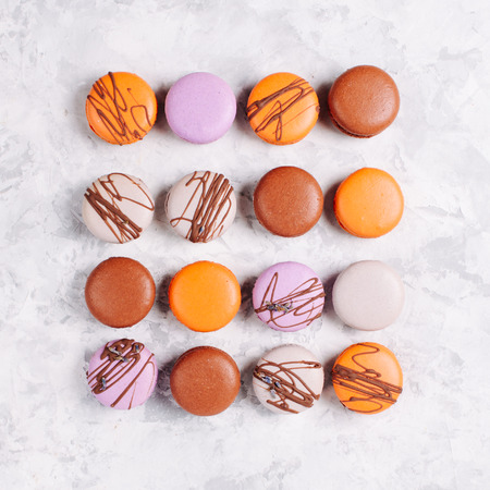 Different types of macaroons: lavander, chocolate and orange on a marble background Stock Photo