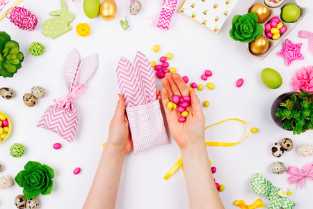 Woman wraps treats in fabric bunny gift bags. Easter concept. Flat lay, top view