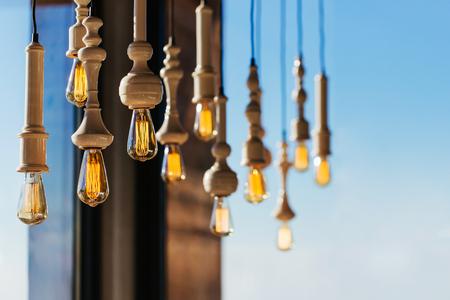Lighting decor. Retro light bulb filament hanging with copy space. Illuminated.