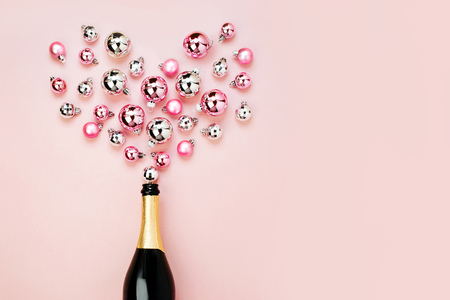 Champagne bottle with pink and silver christmas balls. Flat lay, top view trendy holiday concept.