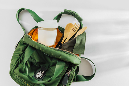 Green backpack with  bamboo cutlery  and  reusable coffee mug. Sustainable lifestyle. Zero waste, plastic free concept. Stock Photo