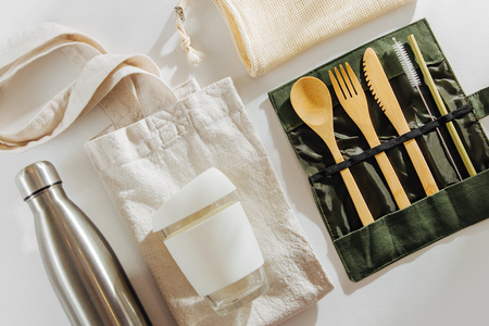Set of Eco friendly bamboo cutlery, eco bag  reusable coffee mug  and  water bottle. Sustainable lifestyle.  Plastic free concept. Stock Photo
