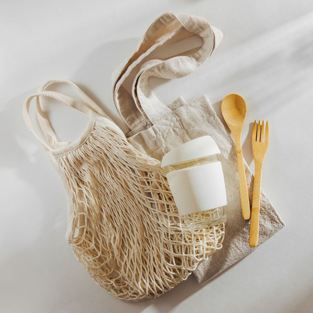 Eco friendly bamboo cutlery, eco bag and  reusable coffee mug. Sustainable lifestyle.  Plastic free concept.