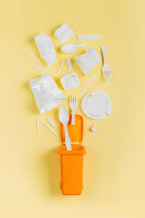 White single use plastic in garbage bin on yellow background.Concept of Recycling plastic. Flat lay, top view