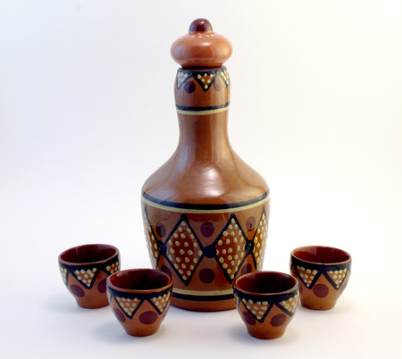 ceramic bottle: ceramic bottle with small ceramic cups covered with ornament Stock Photo