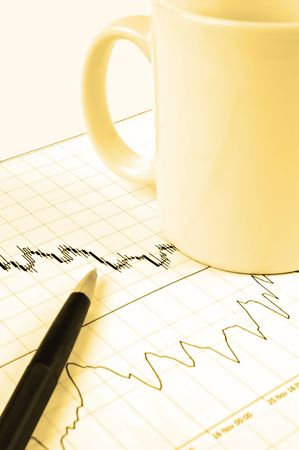Pen and cup on Forex candlestick chart in yellow lighting