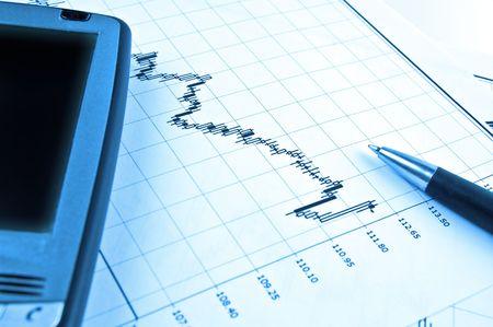 PDA en pen op Forex kandelaar grafiek in blauwe verlichting Stockfoto