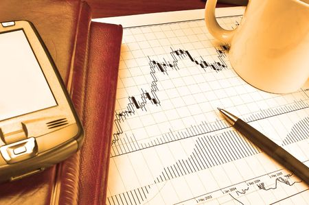 PDA and notebooks on Forex candlestick chart in yellow lighting