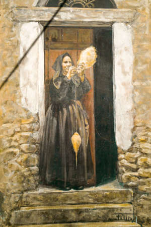 Painting of old woman standing in front of doors. Beautiful drawing on house facade. Snapshot from Fonni town streets, Sardinia, Italy.
