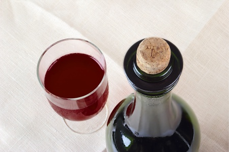 Glass and bottle with red wine close up