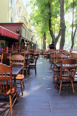 empty sidewalk restaurant is photographed with diminishing perspective early in the morning.