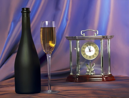Glass of champagne and bottle.Red- blue background with hours Stock Photo - 11246218
