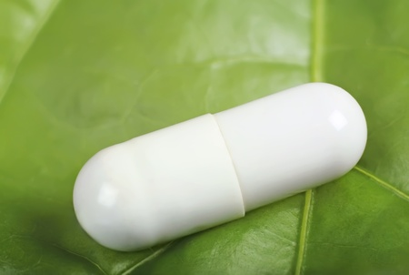 Capsule from a vegetative medical product on green sheet Stock Photo
