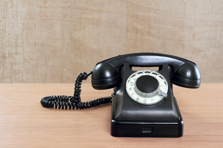 Still-life with old phone on a beige background Stock Photo