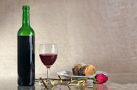 bottle with red wine and a glass against a sacking