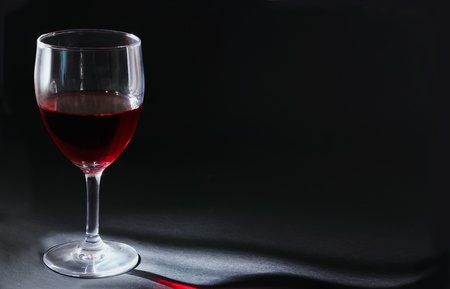glass half full: glass with red wine on a black background
