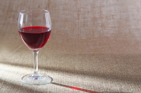 glass of red wine against a rough sacking Stock Photo