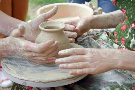 Hands of two people create pot on potter