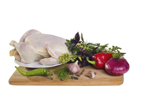 Raw chicken with vegetables on cutting board isolated on white