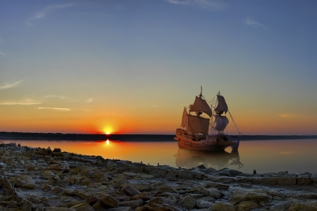 The ancient ship in the orange light of the setting sun. Stock Photo