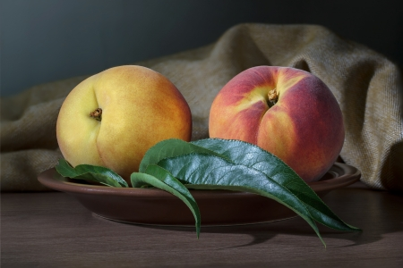 Two ripe peach with leaves on a ceramic plate Stock Photo