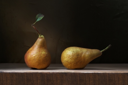 Two ripe yellow pears on a wooden table