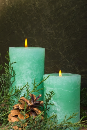 Two christmas candles on a dark green background