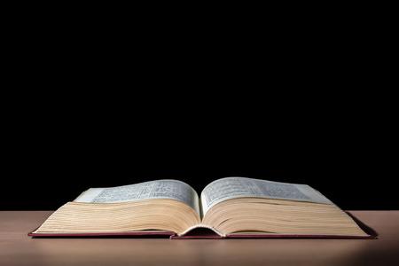 黒の背景でテーブルに 1 つ開いている聖書