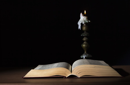 open book illuminated by candle in retro candlestick photo