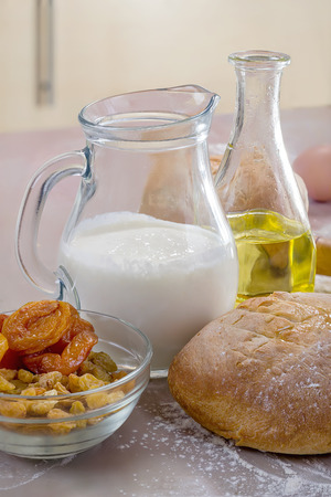 Homemade bread, yogurt, oil and raisins on the table Stock Photo
