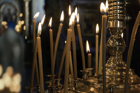 Several tall candles lit in a dark room in church photo