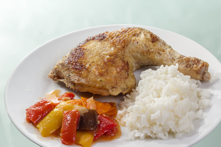 Roast chicken thigh with rice and vegetables on a white plate. Stock Photo