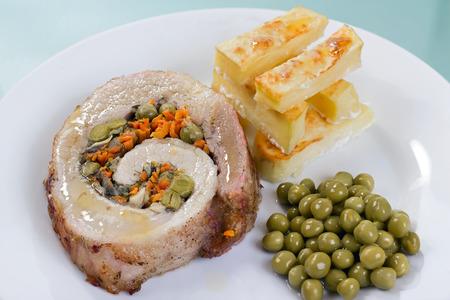 pastel de carne: Vista de primer plano de pastel de carne a casa con patatas asadas y guisantes.