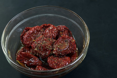 sundried: Sun-dried tomatoes, marinated in olive oil on a dark background.
