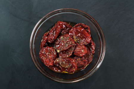Sun-dried tomatoes, marinated in olive oil on a dark background.