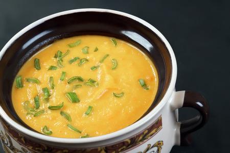 Pumpkin cream soup with green onion closeup