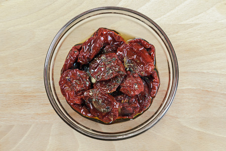 sun dried tomatoes with olive oil on wooden surface