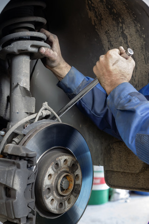 Hands mechanics repaired the brakes on a passenger car Stock Photo