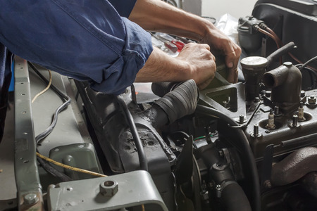 Auto mechanic working under the hood of an old car engine.