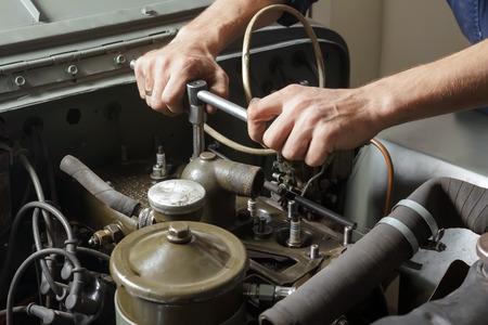 mecanico: Mecánico auto que trabaja bajo el capó de un motor de coche viejo. Foto de archivo