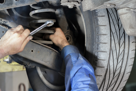 Hands mechanics to repair the suspension on the car Standard-Bild