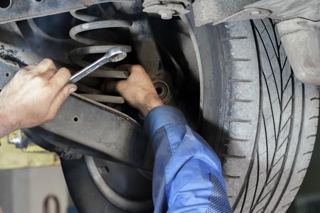 Hands mechanics to repair the suspension on the car Archivio Fotografico