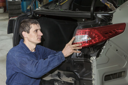 Young mechanic installs tail light on the vehicle.